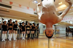 A dancing coach demonstrates a move for his students during a training session at a pole dancing school in Hefei, Anhui province