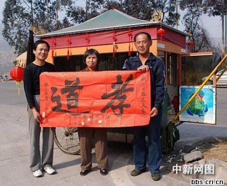 """La famille Wang arborant le mot """"piété filiale"""" - 孝道 xiaodao - devant leur charrette ) bras."""