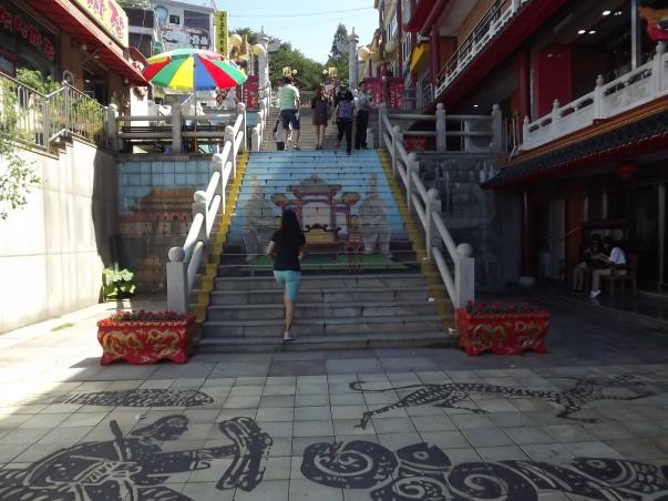 Escaliers conduisant au parc de la Liberté. Sur les marches on peut voir la représentation des fameux soldats en terre cuite de la tombe du premier empereur chinois. Photo © Pauline Kaufmann
